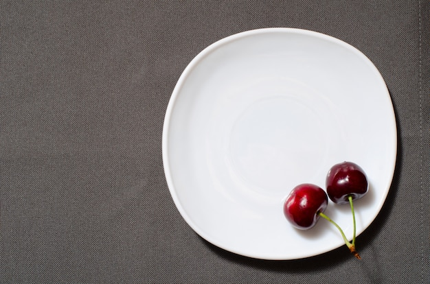 Duas cerejas na borda de um prato vazio na textura cinza, copyspace, vista superior