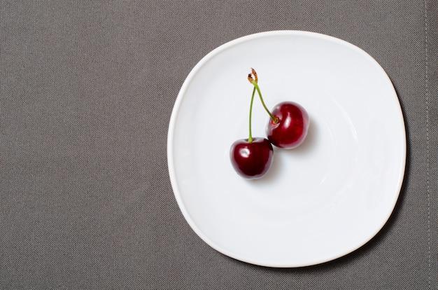 Duas cerejas num prato branco sobre o cinza textura, espaço vazio