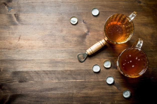 Duas cervejas e abridor com tampas. na mesa de madeira