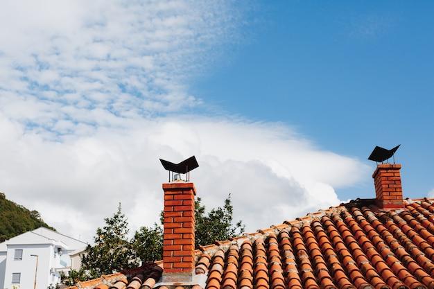 Duas chaminés de tijolo laranja em um telhado de telha e tendo como pano de fundo uma casa branca e um céu azul