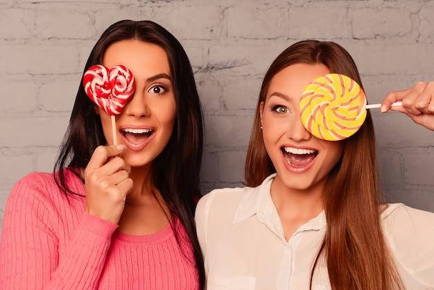 Duas charmosas garotas felizes escondendo os olhos com pirulito e sorrindo