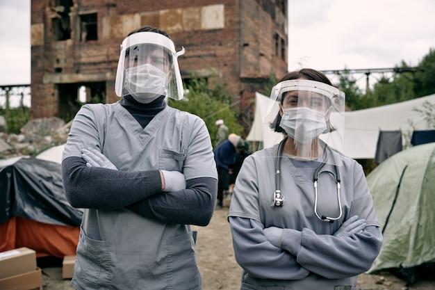 Duas clínicas em trajes de trabalho de proteção em um campo de refugiados