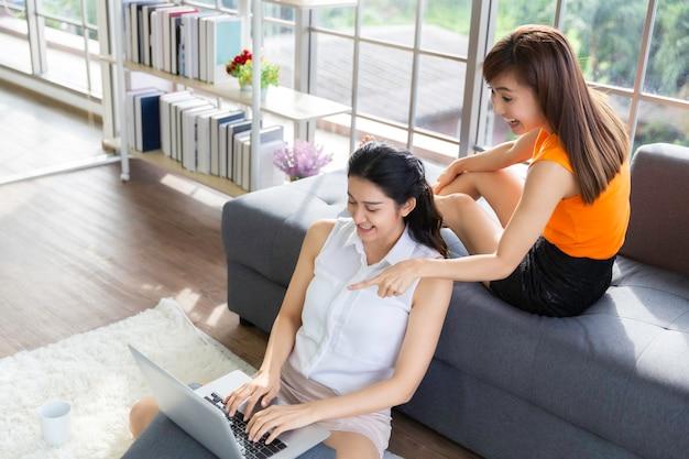 Duas colegas asiáticas sentadas juntas vendo um laptop