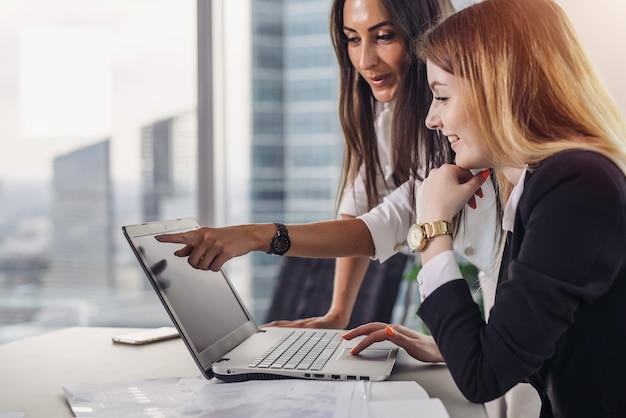 Duas colegas de trabalho femininas apontando para a tela do laptop e rindo durante o processo de trabalho em um escritório moderno.