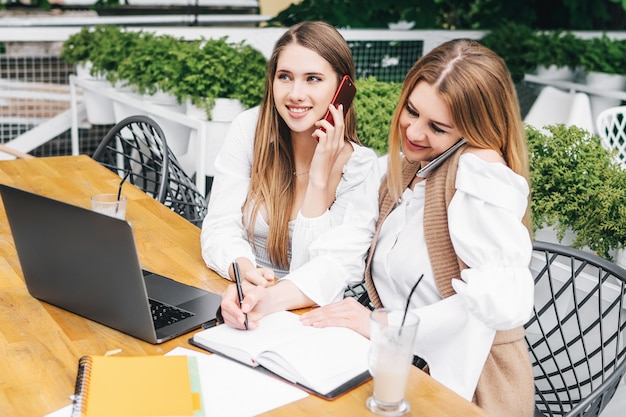 Duas colegas mulheres trabalham juntas no computador, uma delas faz anotações em um caderno