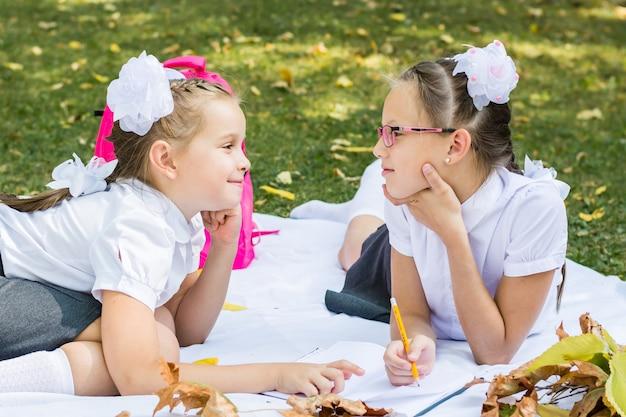 Duas colegiais bonitos estão sorrindo e fazendo lição de casa em um cobertor em um parque ensolarado de outono. educação ao ar livre. conceito de volta às aulas