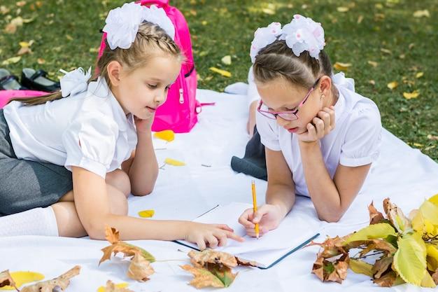 Duas colegiais bonitos fazendo lição de casa em um cobertor em um parque ensolarado de outono. educação ao ar livre. conceito de volta às aulas