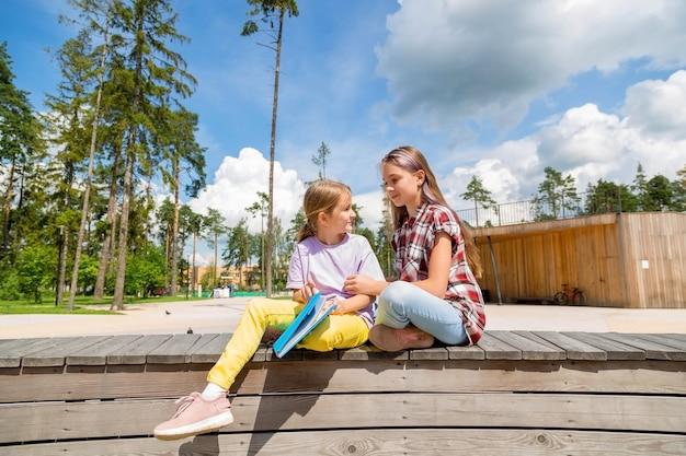 Duas colegiais estão sentadas em um banco do parque, fazendo lição de casa, conversando