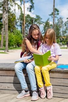 Duas colegiais estão sentadas em um banco no parque, fazendo lição de casa, lendo um livro