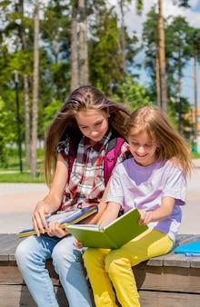 Duas colegiais estão sentadas em um banco no parque público fazendo lição de casa lendo um livro