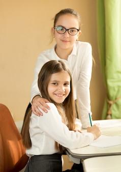 Duas colegiais posando atrás de uma mesa no quarto