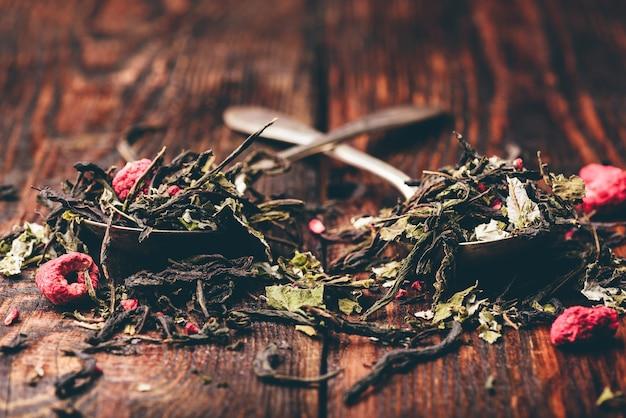 Duas colheres de chá de ervas de framboesa sobre uma superfície de madeira