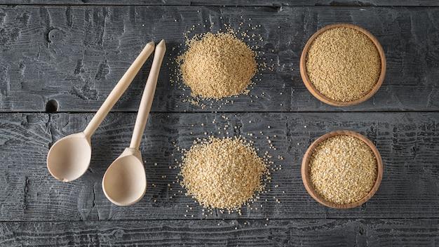 Duas colheres de pau, sementes de amaranto, sementes de quinoa em uma mesa de madeira preta. comida sem glúten.