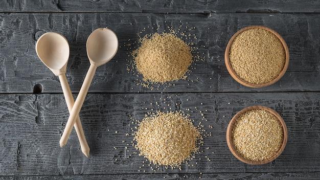 Duas colheres de pau, sementes de amaranto, sementes de quinoa em uma tabela. comida sem glúten.