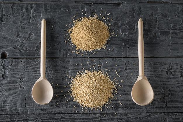 Duas colheres de pau, um monte de sementes de amaranto e um monte de sementes de quinoa em uma mesa de madeira escura. comida sem glúten.