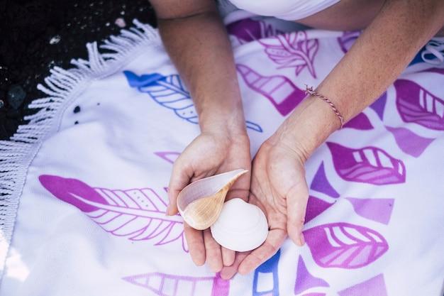 Duas conchas nas mãos de garotas brancas mostradas para a câmera Foto Premium