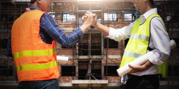 Duas construções apertando a mão.
