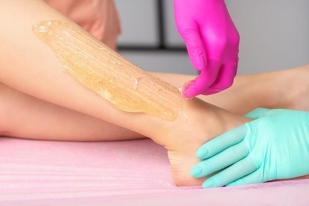 Duas cosmetologistas femininas depilando pernas de mulheres com pasta de açúcar quente em um salão de beleza com spa