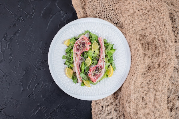 Duas costeletas de carne crua na chapa branca com rodelas de limão e verde.