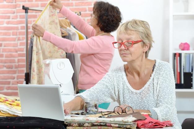 Duas costureiras alegres trabalhando juntos em sua oficina
