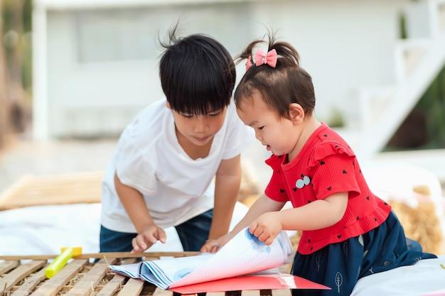 Duas crianças abrem um livro lendo para aprender