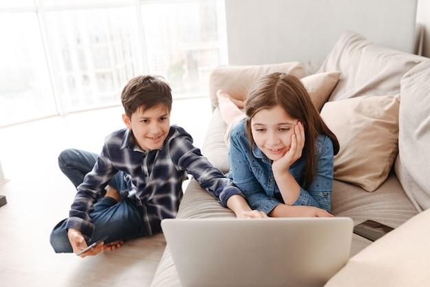 Duas crianças adolescentes, menina e menino, descansando no sofá em casa, enquanto usam o smartphone e o laptop