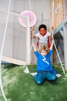 Duas crianças adoráveis de várias etnias em fantasias de super-heróis segurando-se por cordas enquanto brincam juntas