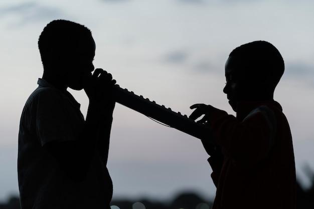 Duas crianças africanas ao pôr do sol tocando instrumento