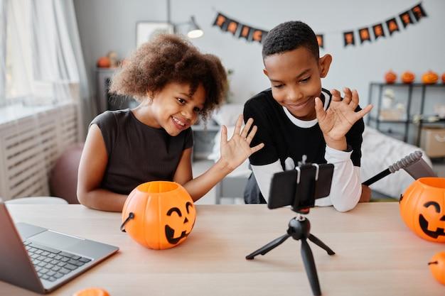 Duas crianças afro-americanas sorridentes acenando para um smartphone enquanto conversam por vídeo em transmissão ao vivo no corredor ...