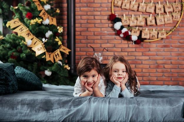 Duas crianças alegres do sexo feminino, deitada na cama com decorações de ano novo e árvore do feriado.