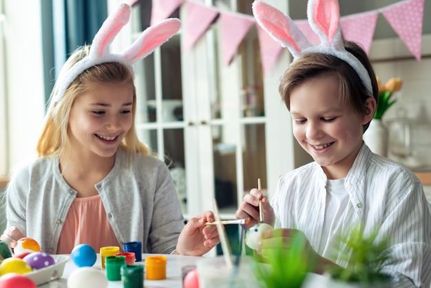Duas crianças alegres pintam ovos de páscoa em orelhas de coelho.