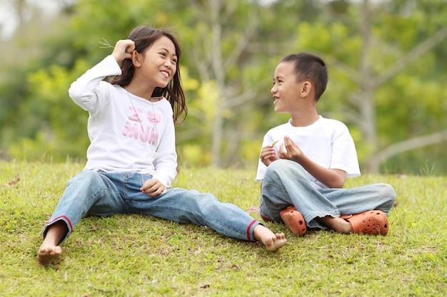Duas crianças ao ar livre, conversando