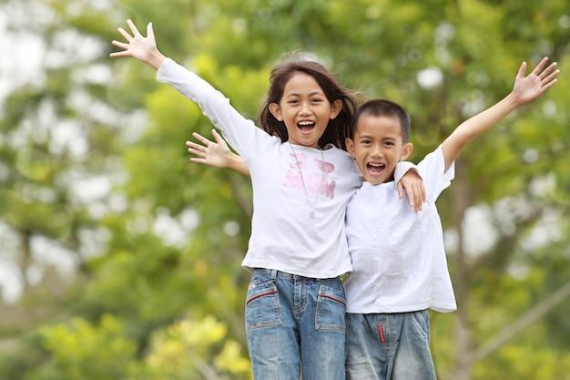 Duas crianças ao ar livre levantam a mão e sorriem