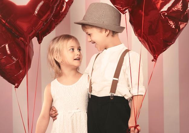 Duas crianças apaixonadas em pé com os balões