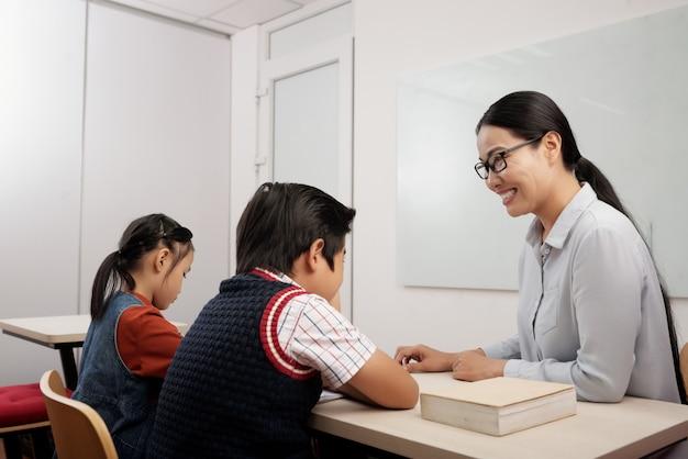 Duas crianças asiáticas sentado na sala de aula e professor sorridente em copos, conversando com o menino