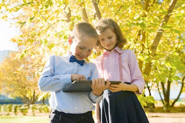 Duas crianças assistindo tablet digital, outono ensolarado parque de fundo