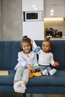 Duas crianças bonitas sentam-se no sofá e brincam com brinquedos. irmãs afro-americanas brincando em casa.