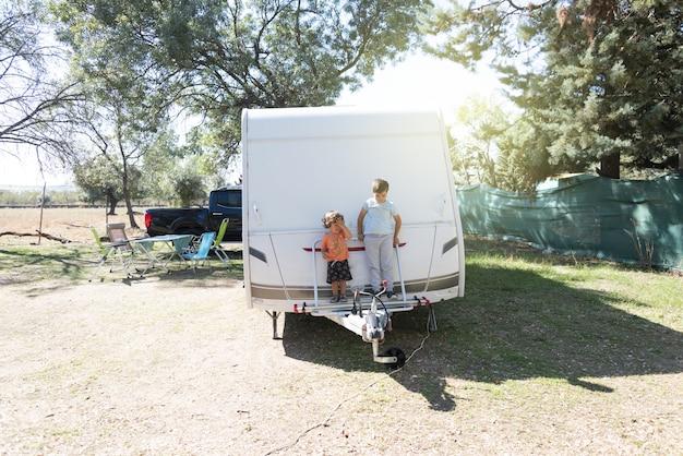 Duas crianças brancas brincam e passam férias alternativas em uma caravana