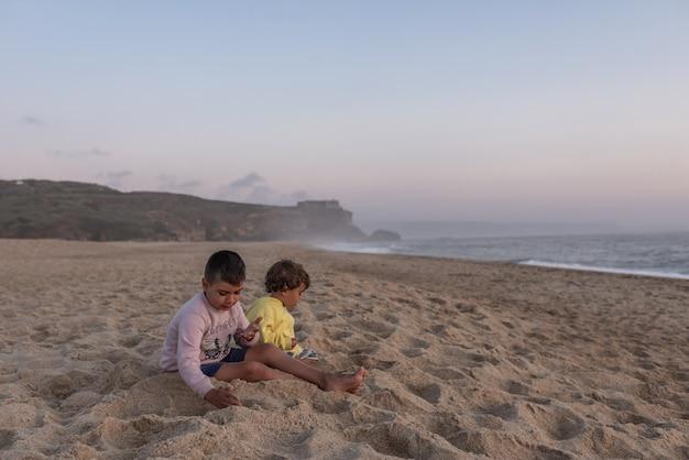 Duas crianças brancas brincando ao pôr do sol na praia