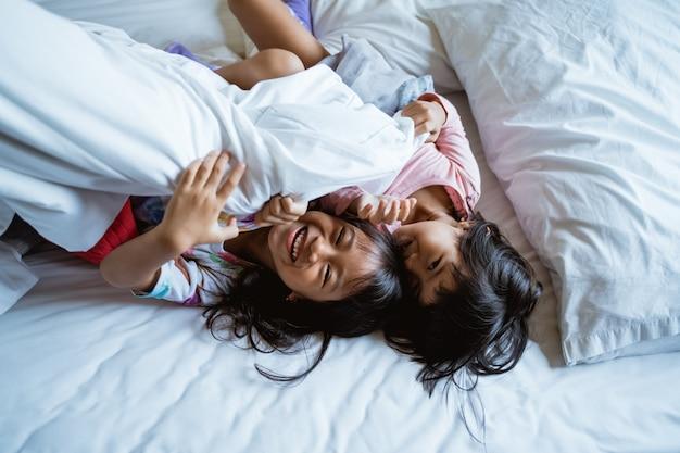 Duas crianças brincam e riem na cama