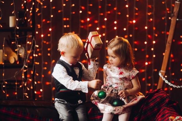 Duas crianças brincando com arcos de natal verde perto de decoração e árvore de natal