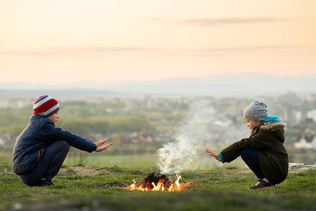 Duas crianças brincando com fogo ao ar livre no frio