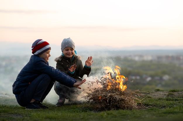 Duas crianças brincando com fogo ao ar livre no tempo frio.