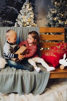 Duas crianças brincando com o natal perto de decoração e árvore de natal