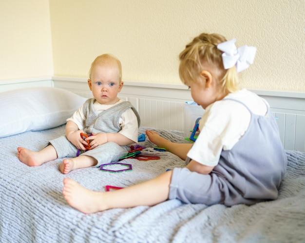 Duas crianças brincando com um brinquedo magnético de construção enquanto estão sentadas na cama