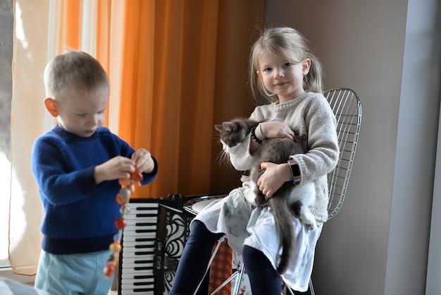 Duas crianças brincando com um gato em casa