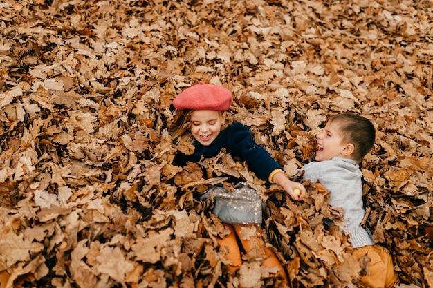 Duas crianças brincando nas folhas