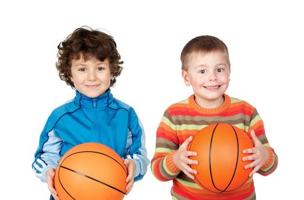 Duas crianças com bolas de basquete