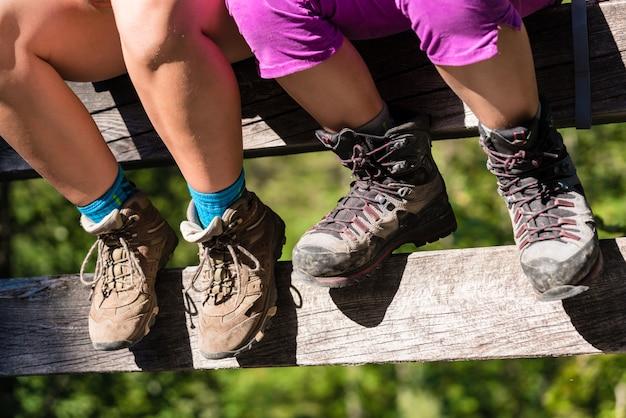 Duas crianças, com, botas hiking, sentando, ligado, trilho ponte