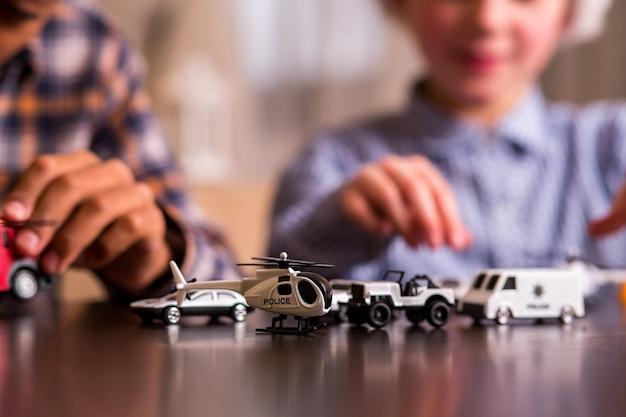 Duas crianças com carrinhos de brinquedo.